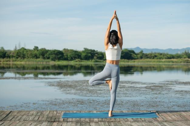 Donna su una stuoia di yoga per rilassarsi nel parco. giovane donna asiatica sportiva che pratica yoga, bella ragazza sorridente in piedi, posa dell'albero, allenamento, allenamento, abbigliamento sportivo, pantaloni e top.