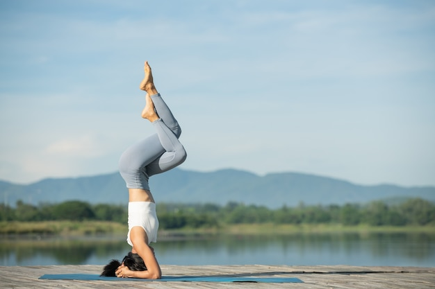 Woman on a yoga mat to relax in the park. young sporty asian woman practicing yoga, doing headstand exercise, working out, wearing sportswear, pants and top.