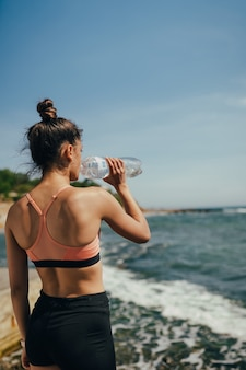 Woman in yoga outfit drinking fresh water from bottle after exercise on beach