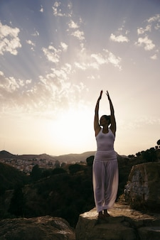 Woman at yoga pose with hands up