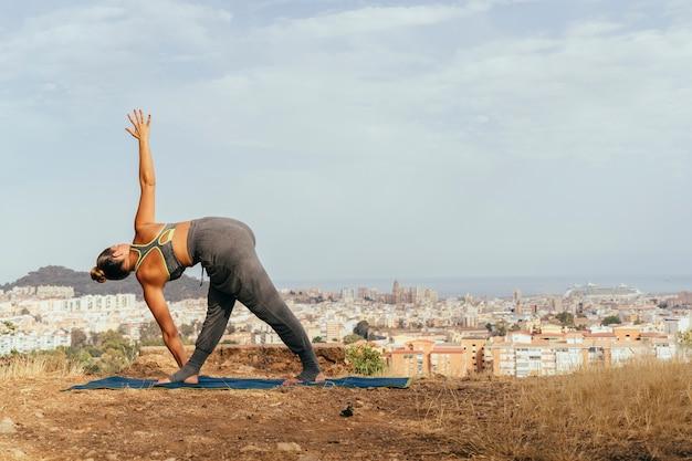 Donna alla posizione di yoga e la città