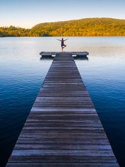 여름 배경 젠 라이프 스타일에서 호수에서 연습하고 명상하는 여성 요가