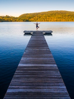 Woman yoga practicing and meditating by the lake in summer background zen lifestyle