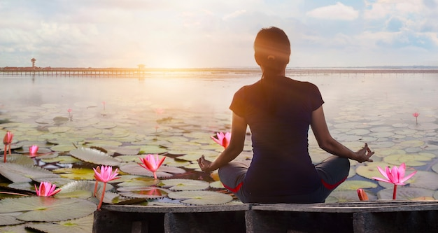 Woman yoga practicing and meditating by the red lotus lake background
