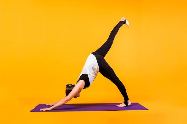 女性ヨギはオレンジ色の壁の紫色のマットでアーサナadhomukhashvanasanaを実行します