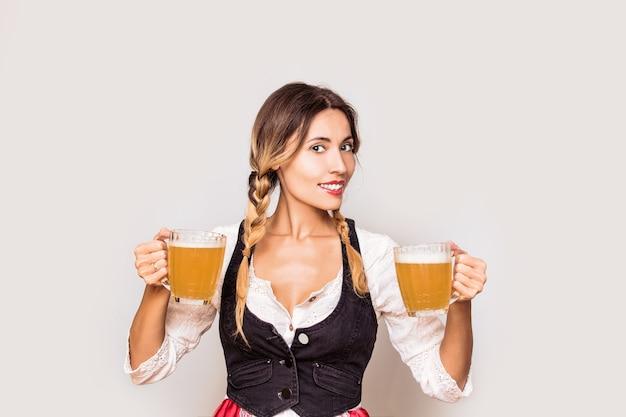 스튜디오에서 옥토버페스트에 조끼와 흰 블라우스 옷에 그의 손에 맥주 잔을 가진 여자 젊은 성인