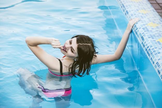 プールのピンクの水着で若い美しいブルネットの女性