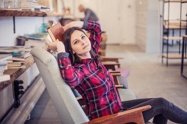 女性の若い美しい学生は、ロフトで休んで新しいアイデアを考えています