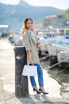 A woman young and beautiful on vacation near the river waiting for a yacht on the background of a tourist boat