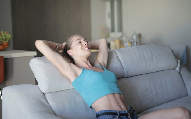 여자 젊은 아름 다운 여자는 소파에 앉아서 쉬고