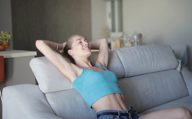 Giovane bella donna della donna che si siede sul sofà e sul riposo Foto Gratuite