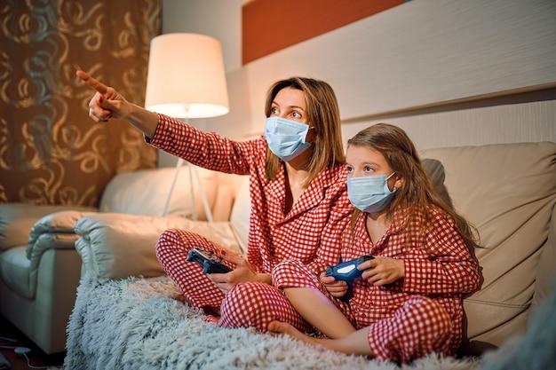 Woman and young girl wearing pajamas and medical protective mask