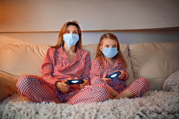 Woman and young girl wearing pajamas and medical protective masks sitting on sofa in living room with video game controllers at home isolation auto quarantine, covid-19