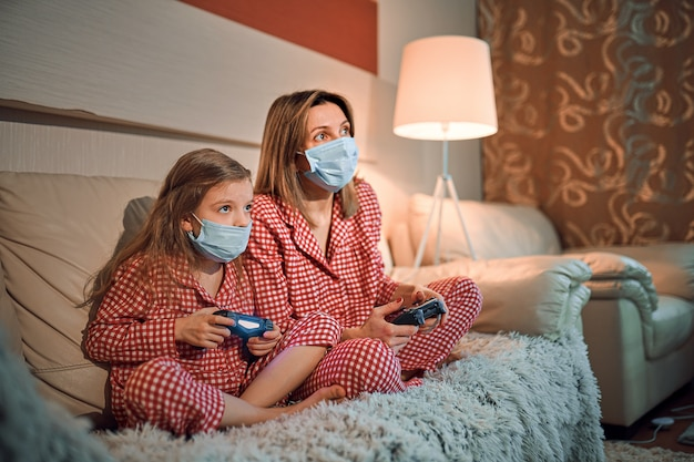 Woman and young girl wearing pajamas and medical protective masks sitting on sofa in living room with video game controllers at home isolation auto quarantine, covid-19.