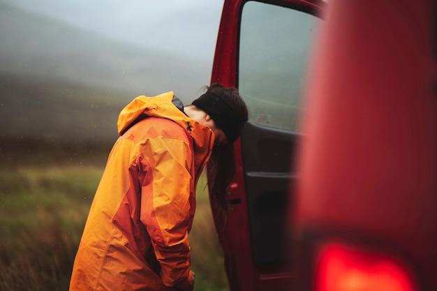 오렌지색 방수 재킷을 잠그고 있는 여성