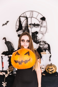 Woman in zombie grim in front of alloween decorations