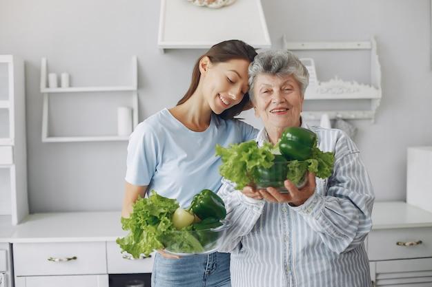 若い孫娘とキッチンで老woman