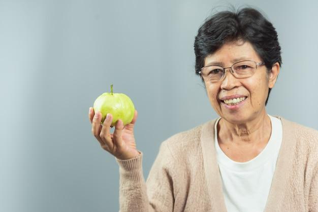 灰色の緑の果物を保持している笑顔の老womanの肖像画