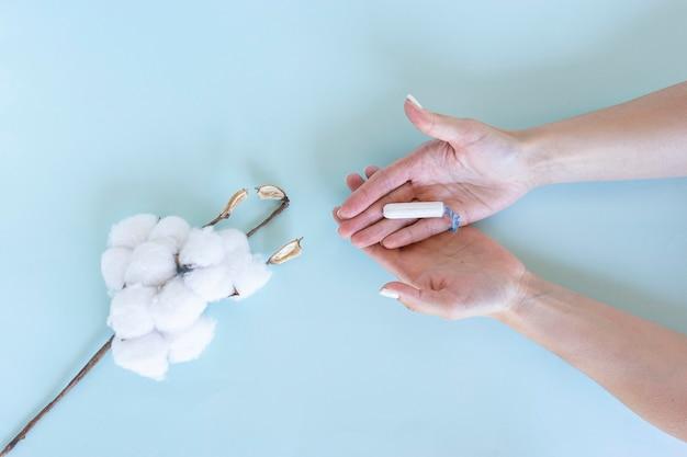 여성의 손은 옆에 면이 놓여 있는 위생 탐폰을 들고 있습니다.