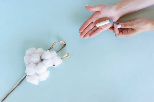 Woman's hand holds a sanitary tampon