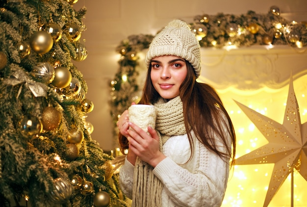 Womanin warm clothes drinking cup coffee at home in new year's decor