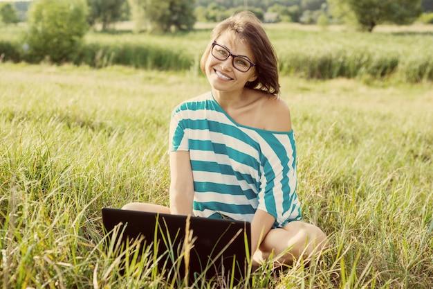 コンピューターに取り組んでいる芝生の上に座っている笑顔のwomanl