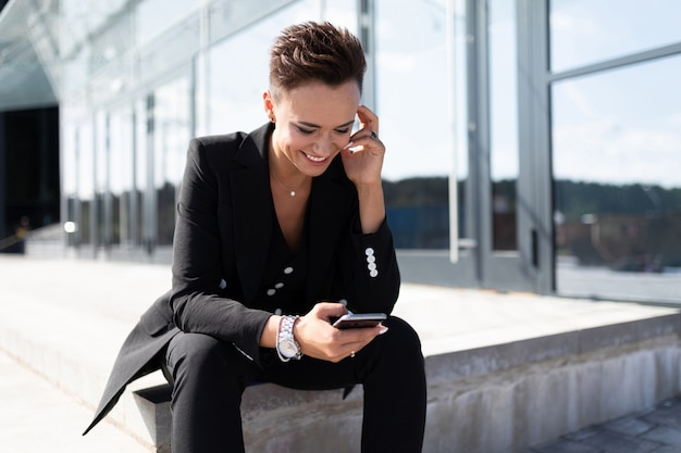Успешный бизнес womanposing на фоне городского современного офисного здания