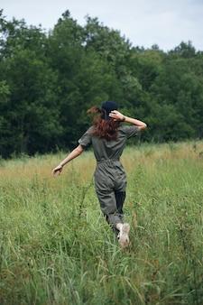 緑のジャンプスーツでフィールドを横切って走る女性自然の太陽の自由の背面図
