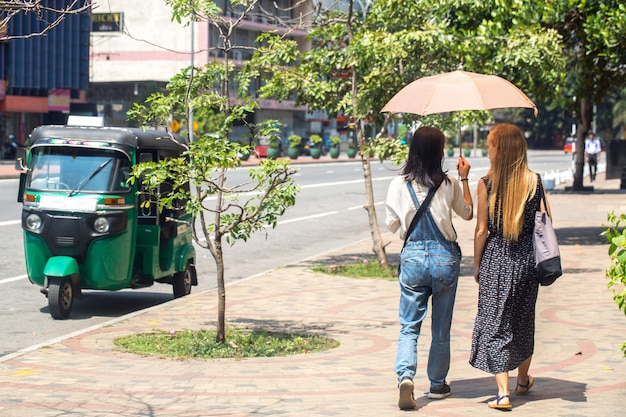 Womans are walking along the road