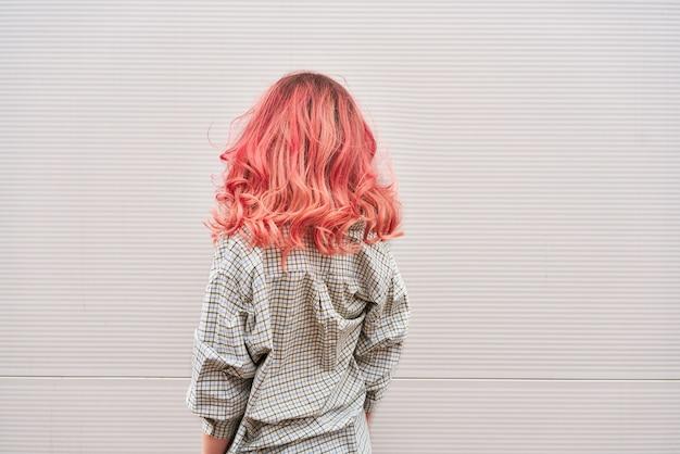 Женщины вернулись с окрашенной розовой прической над серой стеной