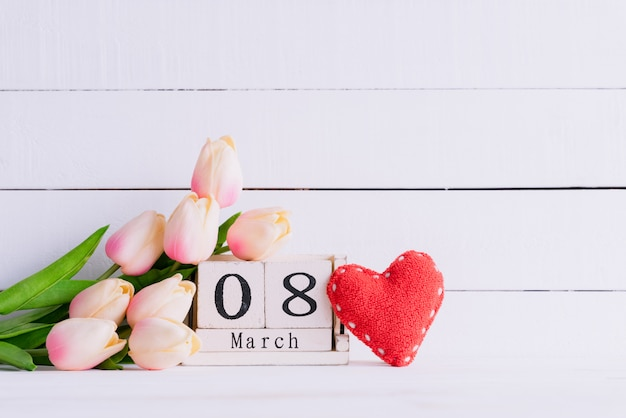 Womans day concept. pink tulips and red heart on wooden background.