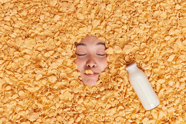 Womans face sticking through cornflakes has healthy nutrition keeps eyes closed drinks fresh milk