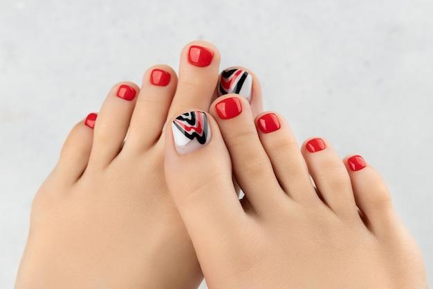 회색 아름다운 여름 빨간 네일 디자인에 여자의 발과 손