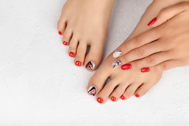 女性の足と手は灰色の美しい夏の赤いネイル デザイン