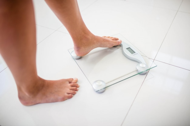 Womans feet going on weighting scale at home