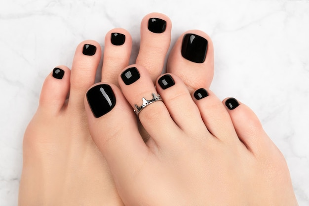 Женские ноги на мраморном фоне. красивый классический черный дизайн ногтей. маникюр, концепция салона красоты педикюра.