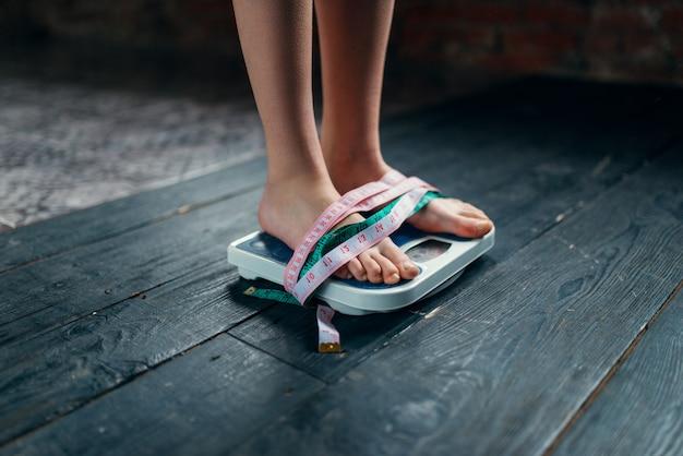 Женские ноги на весах перевязаны рулеткой. концепция сжигания жира или калорий. похудение, жесткая диета