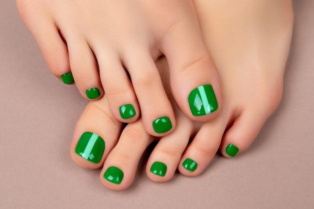 Женские ноги с зеленым лаком для ногтей на коричневом фоне