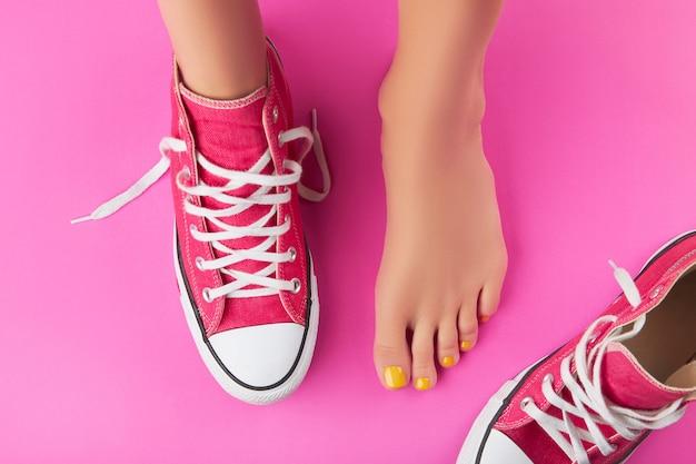 Женские ножки с весенне-летним дизайном ногтей на розовом фоне