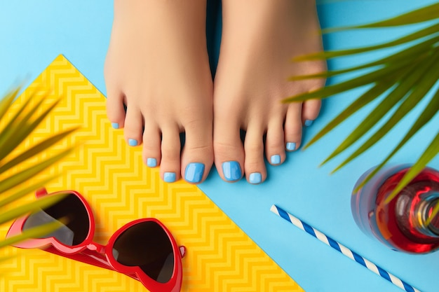 Женские ножки с летними аксессуарами и красивым летним дизайном ногтей