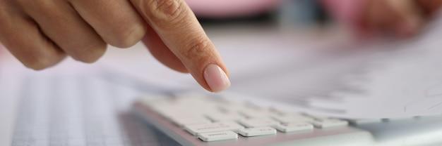 Палец женщины над клавиатурой компьютера содержит документы с бухгалтерским учетом финансовых показателей