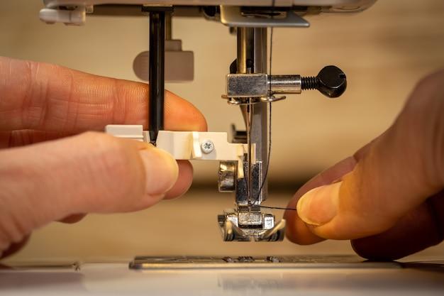 Женские пальцы кладут нить в игольную петлю на современной электрической швейной машине для начала шитья