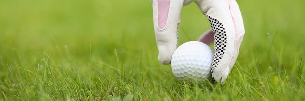 A womans gloved hand puts a golf ball into position bright juicy grass on a golf course