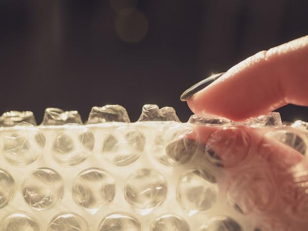 A womans hand bursts bubbles on a bubble wrap