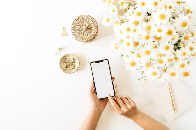 女性の手は空白の画面でスマートフォンを保持します。白い背景の上のカモミールデイジーの花の花束とノートブックとホームオフィスデスクワークスペース