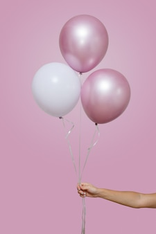 女性の手は、テキスト用のスペースとピンクの背景に分離された3つのピンクと白の風船を保持します