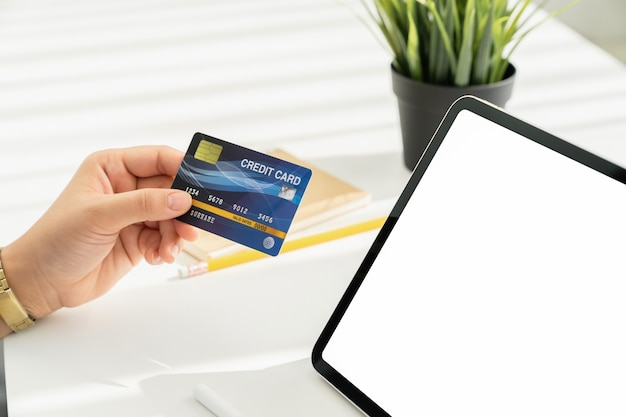 Womans hand holding a credit card and using a tablet for online shopping on a white desk