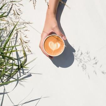 Женская рука держит чашку кофе на белом.