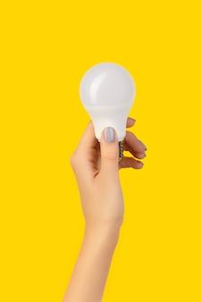 青い背景にled省エネ電球を持っている女性の手。持続可能なライフスタイル環境にやさしいコンセプト