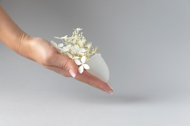 Womans hand holding a menstrual cup cup is containing fresh gentle flowers grey background